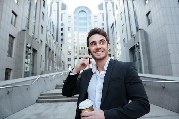 Empresário, segurando o café e telefone