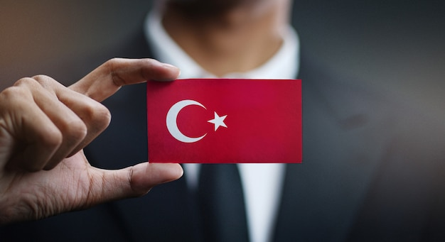 Empresário segurando o cartão da bandeira da turquia