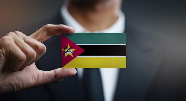 Empresário segurando o cartão da bandeira de moçambique