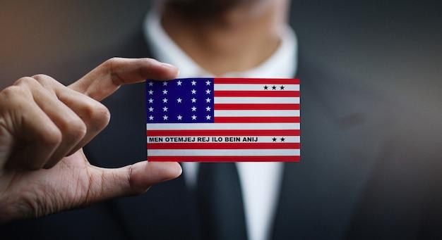 Empresário segurando o cartão da bandeira do atol de biquíni