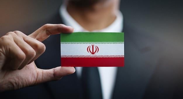 Empresário segurando o cartão da bandeira do irã
