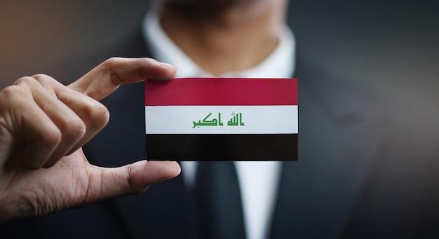 Empresário segurando o cartão da bandeira do iraque