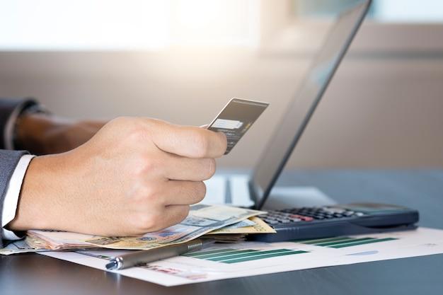 Empresário, segurando o cartão de crédito e digitando no computador portátil