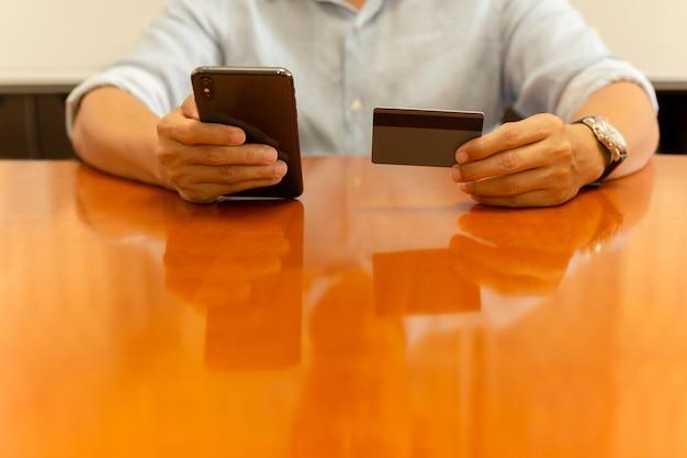 Empresário, segurando o cartão de crédito e trabalhando no celular.