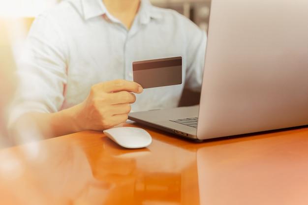 Empresário, segurando o cartão de crédito e trabalhando no laptop para serviços bancários on-line.