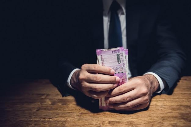 Empresário, segurando o dinheiro, moeda da rúpia indiana, na mesa no quarto escuro