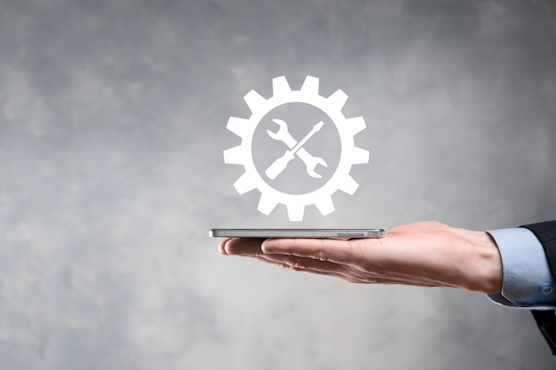 Empresário, segurando o ícone de engrenagem com ferramentas. engrenagem. conceito de diagrama digital de foco de destino, interfaces de gráfico, tela de interface do usuário virtual, rede de conexões.