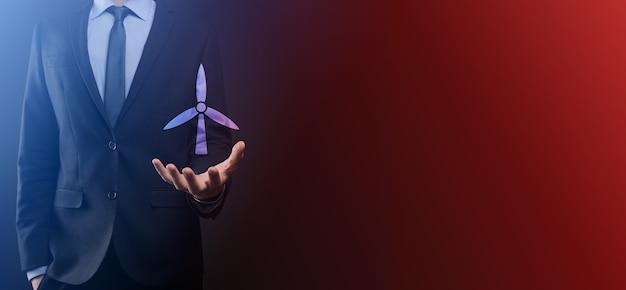 Empresário segurando o ícone de um moinho de vento que produz energia ambiental