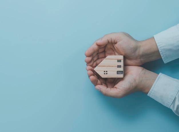 Empresário segurando o modelo de casa de madeira sobre fundo azul, proteger o conceito de casa e ativos.