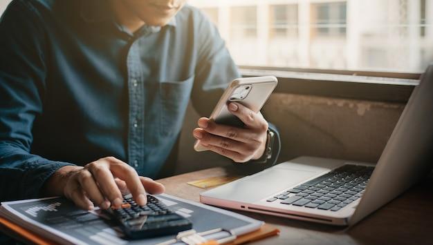 Empresário, segurando o smartphone e o computador, está calculando os custos de investimento da calculadora no escritório em casa.
