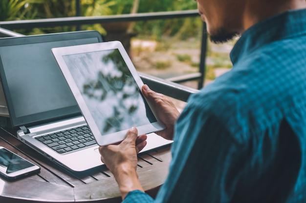 Empresário, segurando o tablet com um celular e laptop em cima da mesa