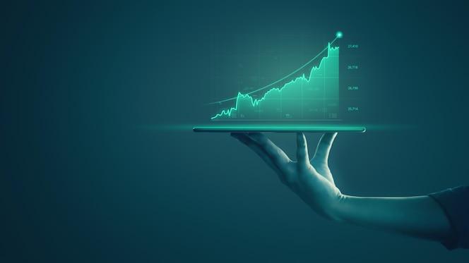 Empresário, segurando o tablet e mostrando gráficos holográficos e estatísticas do mercado de ações, obtém lucros.