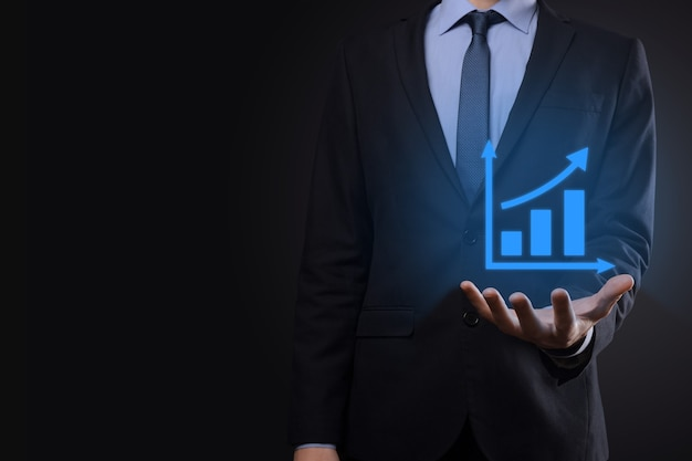 Empresário segurando o tablet e mostrando um holograma virtual crescente de estatísticas, gráfico e gráfico com seta para cima em fundo escuro. mercado de ações. conceito de crescimento, planejamento e estratégia de negócios.