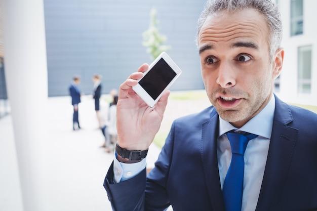 Empresário, segurando o telefone móvel e franzindo a testa