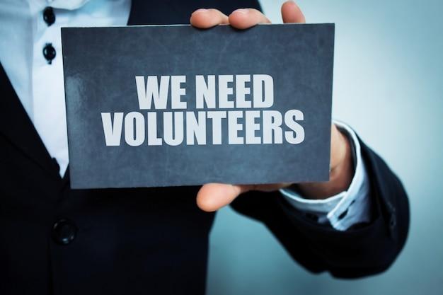 Empresário segurando o texto 'precisamos de voluntários' no bloco de notas