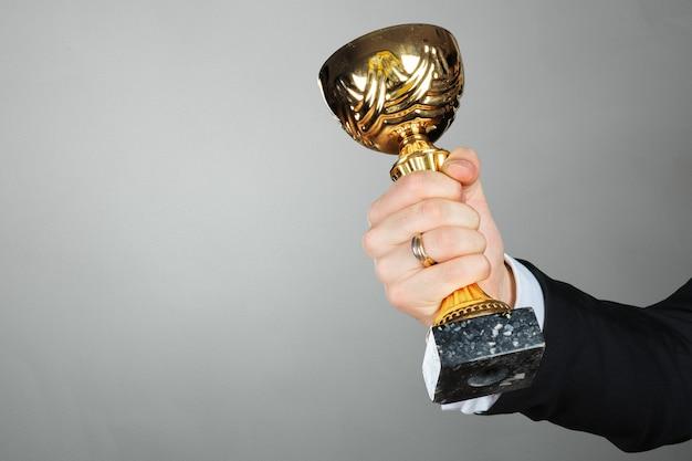 Empresário, segurando o troféu da taça de ouro