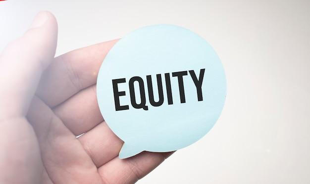 Empresário segurando papel de bolha de discurso com uma mensagem equity