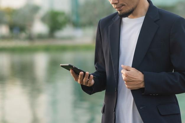 Empresário segurando smartphone ao ar livre no parque urbano