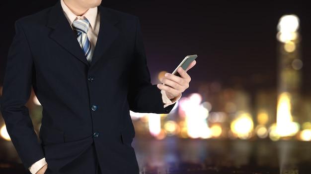 Empresário segurando smartphone ao ar livre