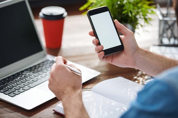 Empresário segurando smartphone e caneta sobre o caderno aberto enquanto planeja o trabalho na mesa na frente do laptop