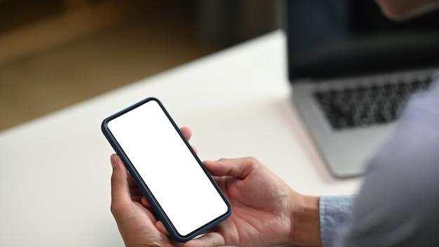 Empresário segurando smartphone na sala de escritório moderno.