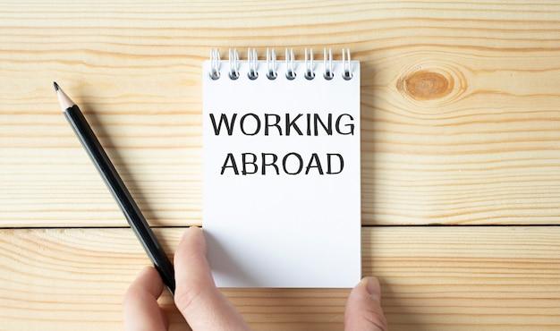 Empresário segurando um bloco de notas branco com texto trabalhando no exterior, conceito de negócio