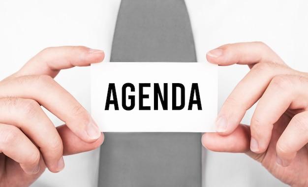 Empresário segurando um cartão com o texto agenda, conceito de negócio