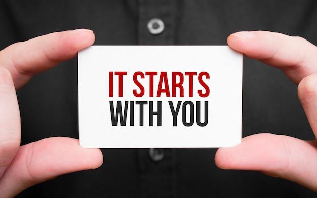 Empresário segurando um cartão com o texto. começa com você, conceito de negócio