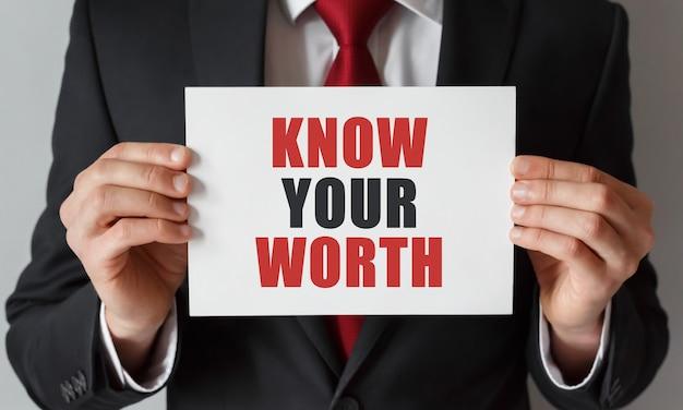 Empresário segurando um cartão com o texto conheça o seu valor