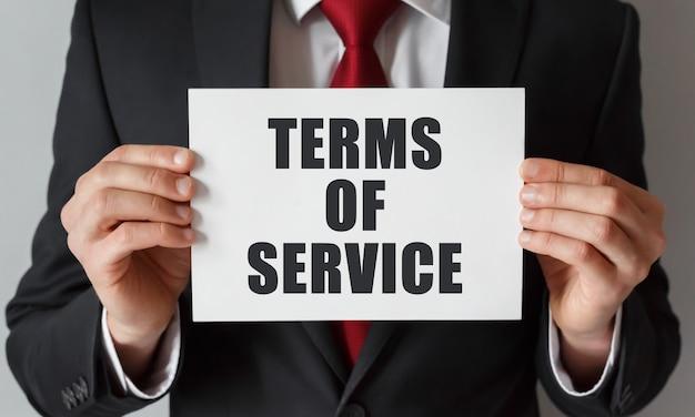 Empresário segurando um cartão com o texto dos termos de serviço