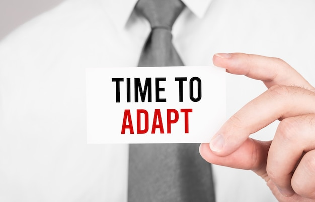 Empresário segurando um cartão com o texto hora de adaptação, conceito de negócio