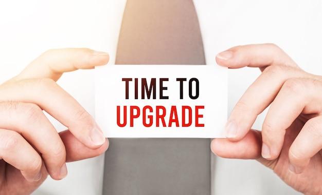 Empresário segurando um cartão com o texto hora de atualizar, conceito de negócio
