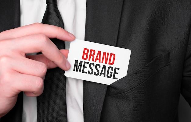 Empresário segurando um cartão com o texto mensagem da marca