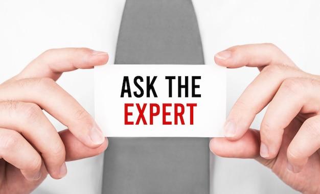 Empresário segurando um cartão com o texto pergunte ao especialista, conceito de negócio