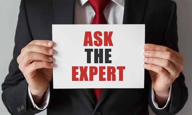 Empresário segurando um cartão com o texto pergunte ao especialista