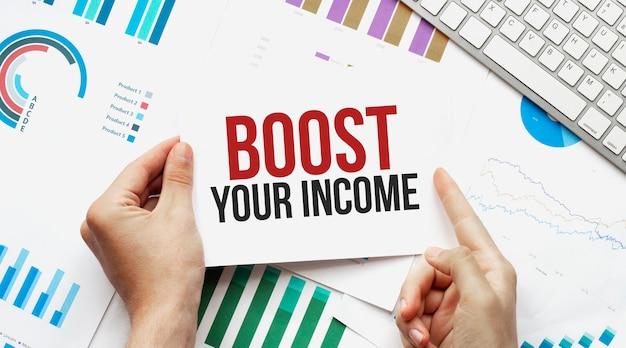 Empresário segurando um cartão com texto aumenta sua renda. teclado, diagrama