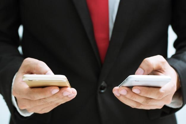 Empresário segurando um celular em cada mão