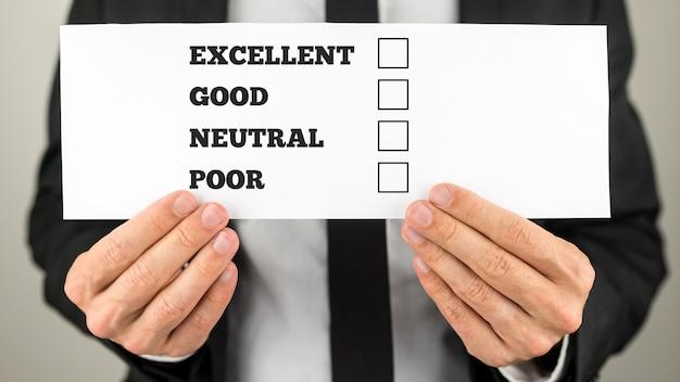 Empresário segurando um cheque de pesquisa com caixas de seleção de múltipla escolha para classificações excelente - bom - neutro - ruim.