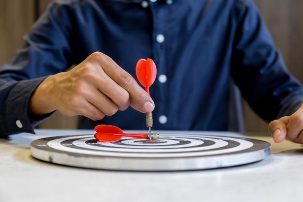 Empresário segurando um dardos, apontando para o centro do alvo