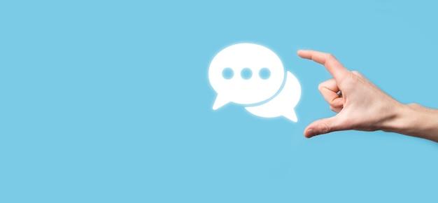 Empresário segurando um ícone de mensagem, bolha fala sinal de notificação em suas mãos. ícone de bate-papo, ícone de sms, ícone de comentários, balões de fala