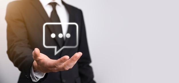 Empresário segurando um ícone de mensagem, bolha fala sinal de notificação em suas mãos. ícone de bate-papo, ícone de sms, ícone de comentários, balões de fala.