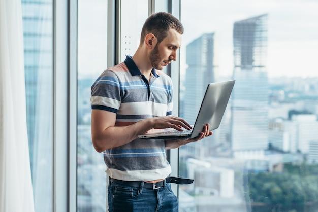 Empresário segurando um laptop trabalhando em pé no escritório perto da janela com vista para a cidade.