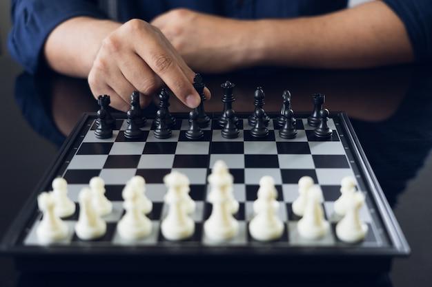 Empresário, segurando um rei xadrez é colocado em um tabuleiro de xadrez.