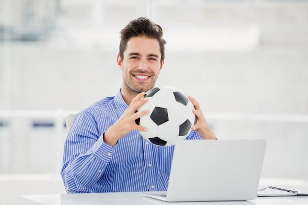 Empresário segurando uma bola de futebol