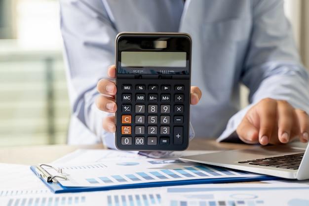 Empresário segurando uma calculadora