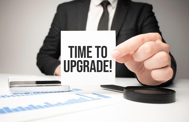 Empresário segurando uma folha de papel com uma mensagem hora de atualizar