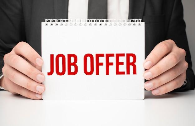 Empresário segurando uma folha de papel com uma oferta de emprego de mensagem