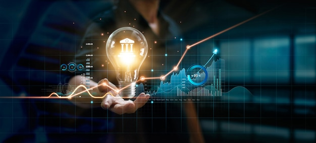 Empresário segurando uma lâmpada criativa com gráfico de crescimento e ícones bancários tecnologia financeira