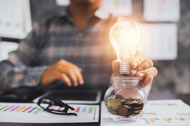 Empresário segurando uma lâmpada em um copo de moedas