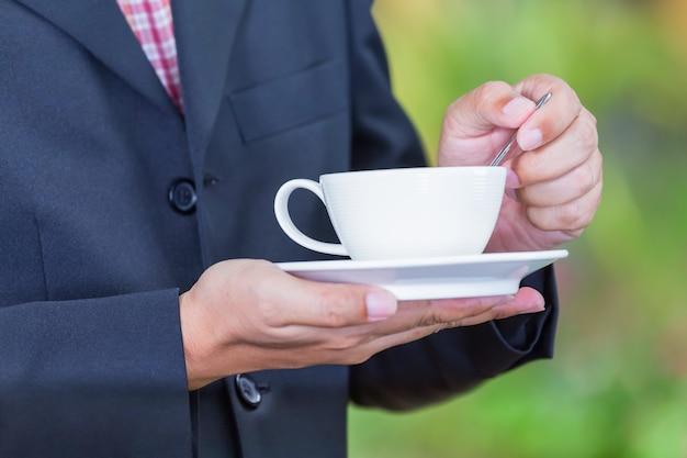 Empresário segurando uma xícara de café para comer um lanche